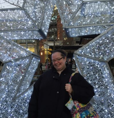 Catherine in a black jacket standing in front of a star covered with lights