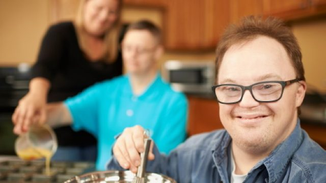 Man whisking with two adults cooking in background