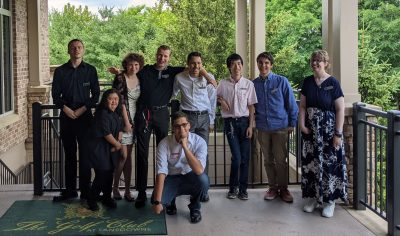9 people stand together for a photo on a terrace at a golf club. They are standing in front of a railing and there are trees in the background.
