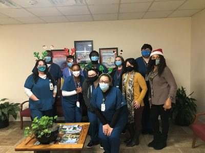 11 people stand together for a photo. Some are wearing reindeer ears or Santa hats. They are all wearing masks. They are in a hospital waiting room with chairs, a table and green plants.