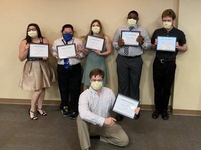 A group of 6 students stands together for a photo in front of a wall. One student is kneeling in front. They are holding up certificates and all are wearing masks.