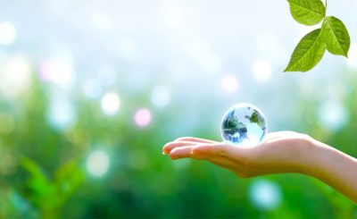Earth crystal blue glass globe in human hand and fresh green leaf on blurred sky and trees background. Saving environment and clean green planet concept.