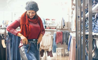 Woman putting on and shopping for new pants.