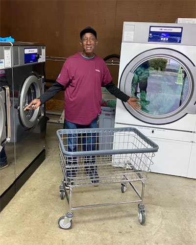 Richard in a red shirt standing in front of washing machines