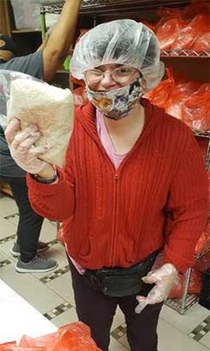 Didlake Volunteer holding rice at House of Mercy's food pantry in Manassas, Virginia.